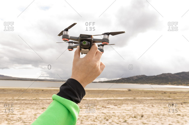 Cropped hand of anonymous person holding drone in beach