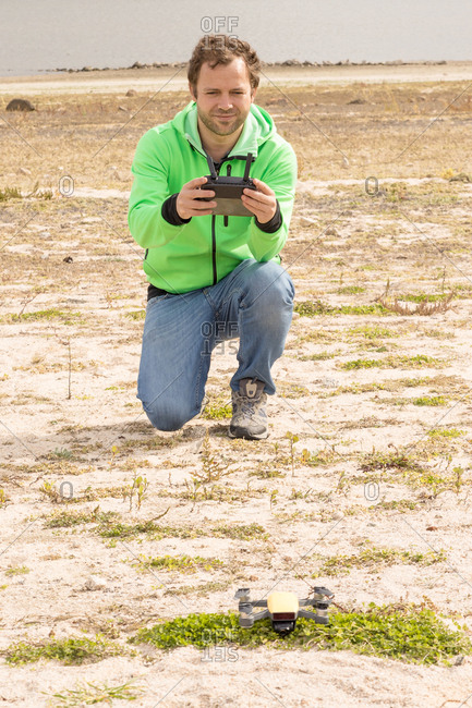 Immersed keen man lifting drone with camera from land using remote control panel in beach