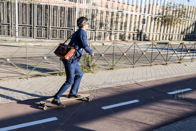 Content stylish businessman in dark blue classy suit on longboard driving down paved roadway in bright day