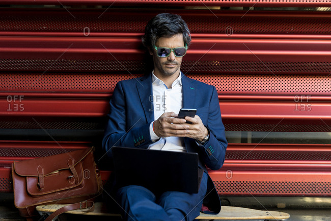 Smart businessman in elegant suit and sunglasses working on laptop and on the mobile phone comfortably placing on longboard leaning on metal red wall in sunny day