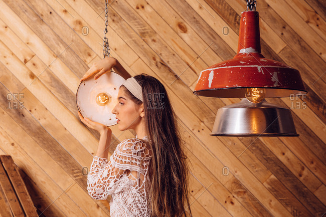 Young woman posing between ceiling lamps on wooden background