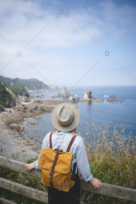 From above back view of anonymous female traveler in hat and backpack leaning in wooden fence on hilltop while looking into sea distance in Asturias, Spain