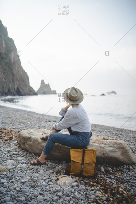 Side view of unrecognizable dreaming stylish female tourist in hat enjoying seascape while chilling on big stone on rocky shore of Asturias looking away