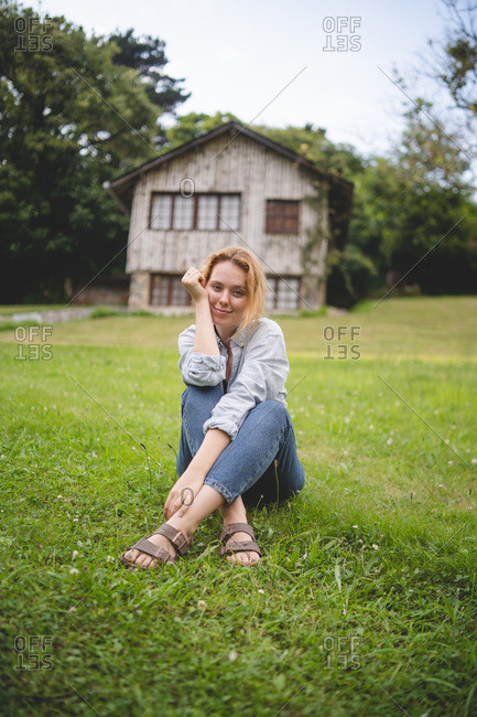 Casual calm young lady enjoying sitting on green meadow near wooden house in rural village in Asturias, Spain