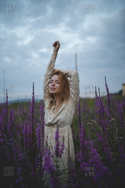 Happy sensual tender redhead woman with closed eyes enjoying smell of salvia blossom in meadow of Asturias, Spain