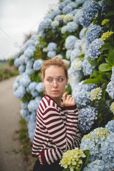 Side view of thoughtful beautiful gentle redhead woman standing beside big blue flowers of hydrangea in Asturias, Spain countryside looking away