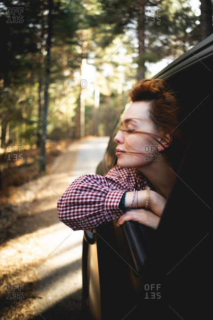 Side view of calm graceful carefree ginger woman enjoying wind and freedom while popping out car window during riding on forest road in Asturias, Spain
