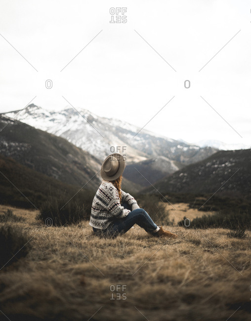 Side view of faceless lady in hat looking away on mountains while resting on brown grass and enjoying picturesque view of Asturias, Spain