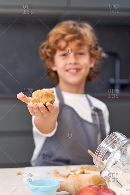 Joyful curly haired boy in apron holding on hand clump of brown dough while smiling and standing near table with cooking things at kitchen