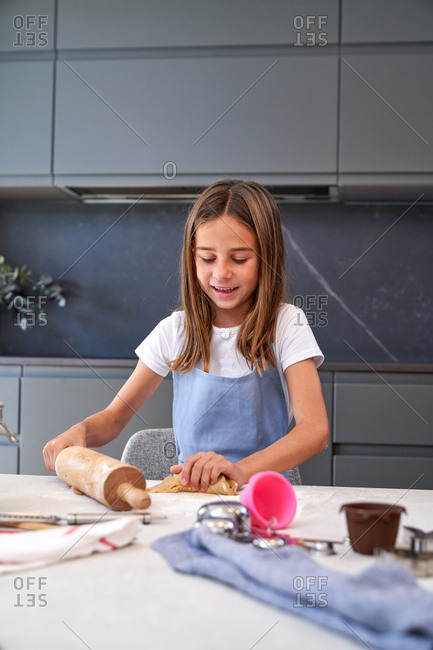 Concentrated brown haired girl in blue apron standing and rolling dough with wooden pin at modern kitchen