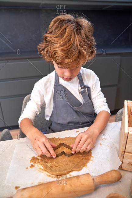 From above of red curly haired little boy in grey apron making cookies with muffin tin on table and smiling at modern kitchen