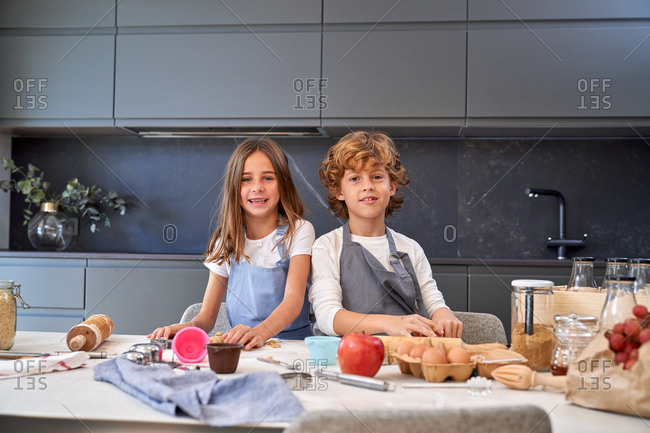 Little male and female kids in back splashes making paste while using different cooking implements at modern kitchen