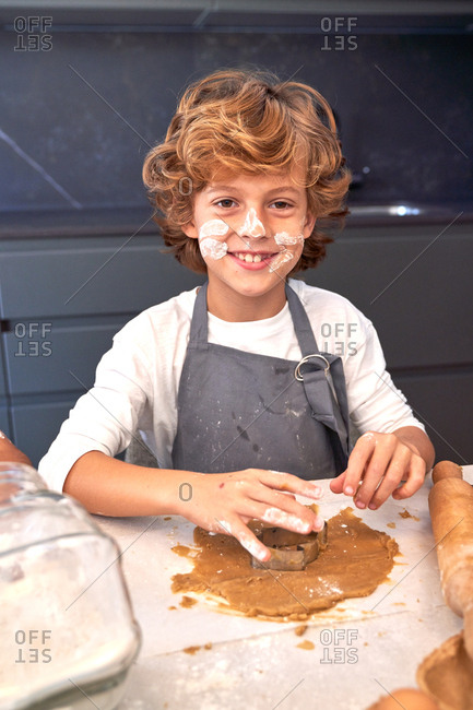 Content boy with face painting dirty flours trying to mold brown paste on table with cooking things at kitchen