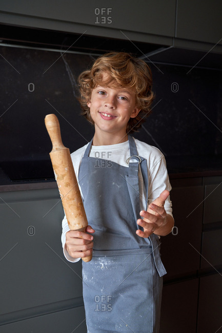 Content red curly haired male kid in apron standing with rolling pin in hand smiling and looking at camera at stylish kitchen