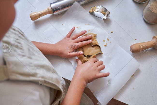 From above unrecognizable cropped hands of child modeling cookies with muffin tin on table at kitchen