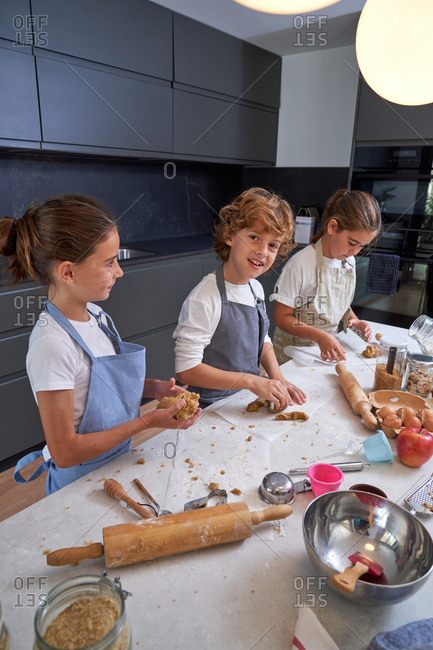 Content male and female children in aprons having fun molding cookies at modern kitchen at home