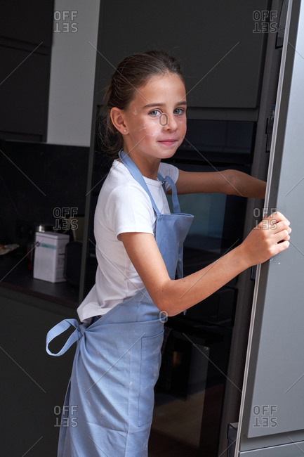 Little girl in apron searching ingredients in closet and looking at camera at modern kitchen