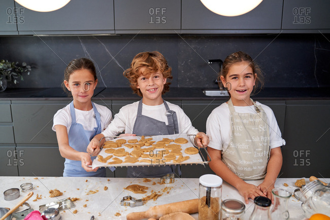 Children in aprons holding tray with cookies on cookie sheet ready to put into the oven at modern kitchen