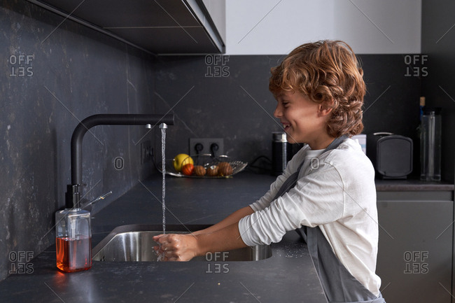Side view of cheerful red curly haired male kid in grey apron opening tab to wash hands at modern kitchen