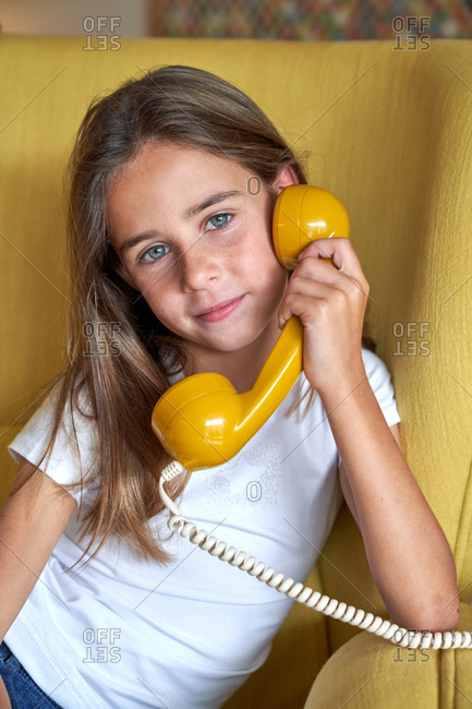 Little girl in white t shirt and jeans sitting on yellow comfortable armchair and talking on telephone and looking at camera