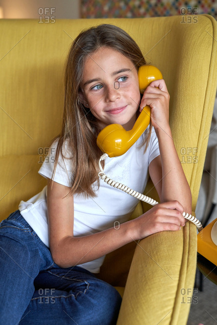 Little girl in white t shirt and jeans sitting on yellow comfortable armchair and talking on telephone and looking away