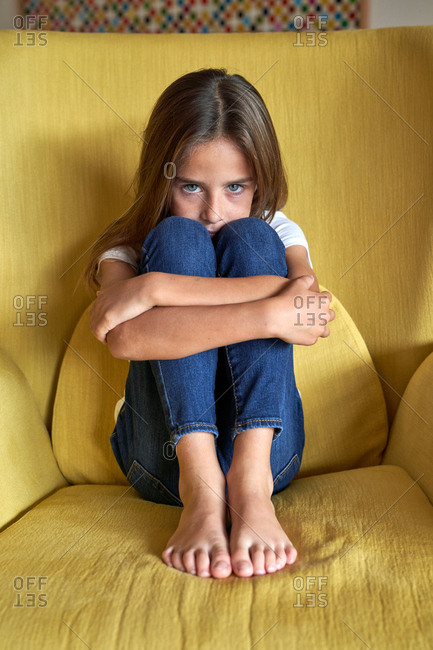Wistful little girl in white t shirt and jeans sitting with tighten legs and grabbing legs with hands on yellow armchair and looking at camera