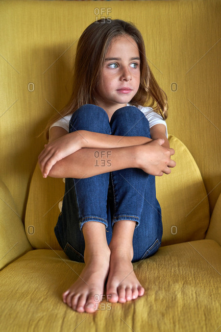Wistful little girl in white t shirt and jeans sitting with tighten legs and grabbing legs with hands on yellow armchair and looking away