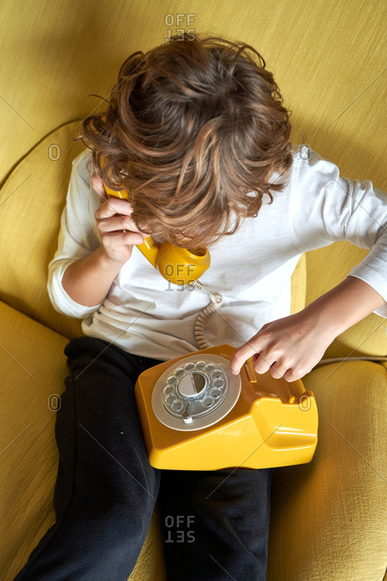 From above anonymous little boy in white t shirt and jeans sitting on yellow comfortable armchair and talking on fusty telephone and looking away