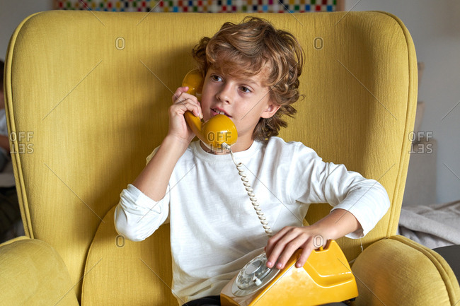 Little boy in white t shirt and jeans sitting on yellow comfortable armchair and talking on fusty telephone and looking away