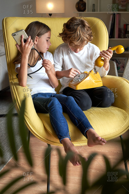 Smart sister and brother sitting in yellow armchair while browsing mobile phone and talking on telephone at living room