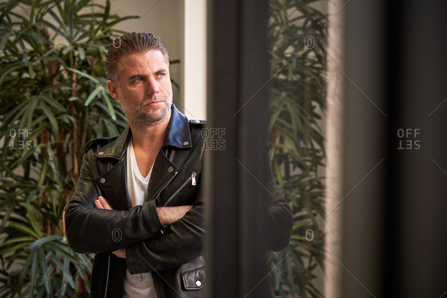 Serious brutal unshaven male in white shirt and black leather jacket with arms crossed looking away against blurred interior in modern building