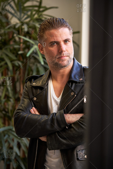 Serious brutal unshaven male in white shirt and black leather jacket with arms crossed looking at camera against blurred interior in modern building