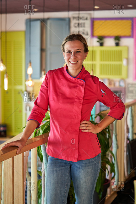 Charming adult female cook in vivid pink uniform with pen in pocket looking at camera and smiling against colorful blurred kitchen interior