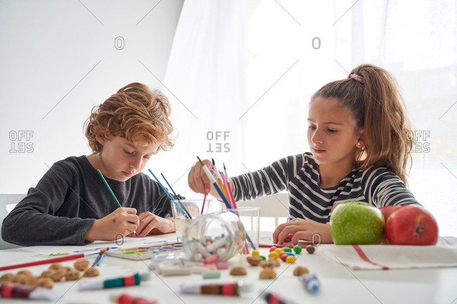 Concentrated girl and boy in casual outfit painting with watercolor while sitting at table with spilled candies and apples at home