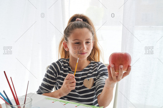 Serious little girl with ponytail looking at apple and thinking while sitting at table and painting against white background at home