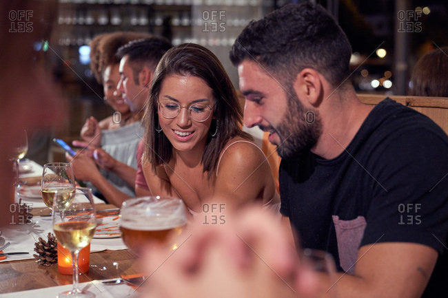 Male and female friends laughing while sitting at festive table at restaurant having dinner