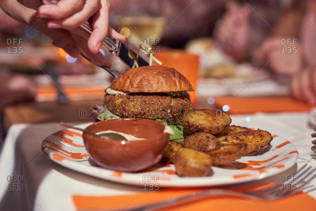 Crop hands cutting tasty hamburger on plate with potatoes and sauce on festive table at restaurant