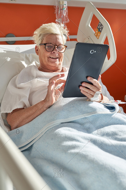 Mature female in glasses smiling and browsing tablet while lying on bed under blanket in hospital ward