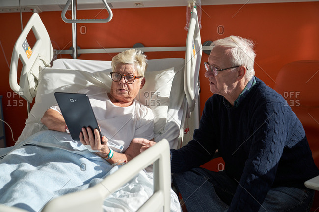 Senior couple using devices in hospital ward