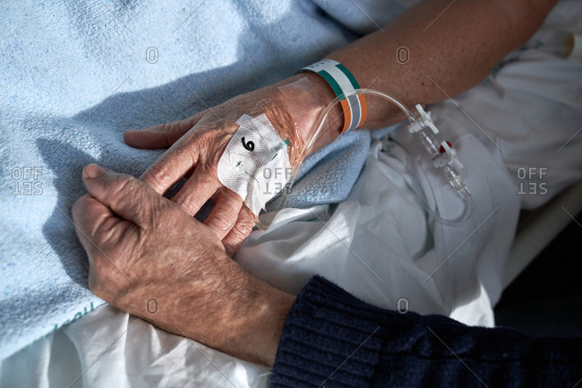 From above mature male holding hand of ill female on bed while visiting patient in hospital ward