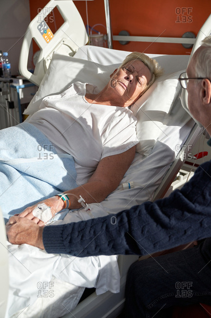 Crop senior man holding hand of sick woman in hospital