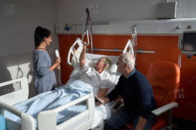 Adult woman and senior man visiting recovering mature female patient in modern ward of hospital