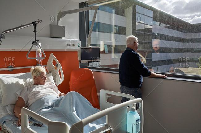 Elderly couple talking in hospital ward