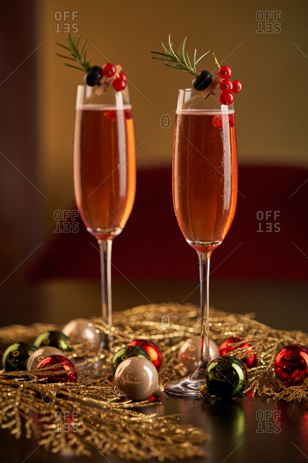 Pair of glasses of red cocktail decorated with berries and green herbs placed on black surface with green and gold tinsel and Christmas balls against blurred gold background