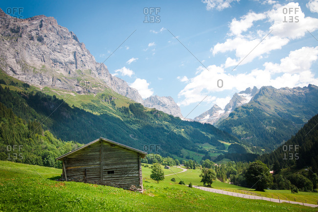 Scenery morning view of abandoned cabin on green meadows with road leading to alps peaks in Switzerland