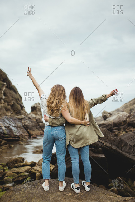 Back view of anonymous women standing on stone on hill and hugging after walking in countryside on cloudy spring day and enjoying time together on cloudy spring day