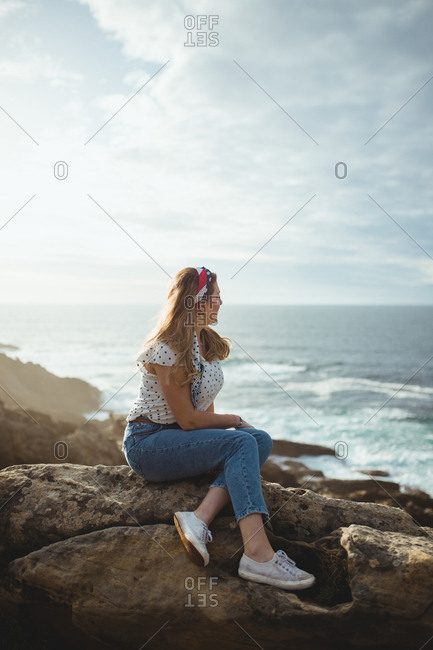 Side view of young female in casual clothes relaxing and dreaming while sitting on stone and looking at sea waves in sunny day with clouds on sky