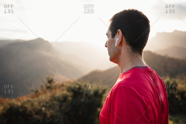 Side view of sportive man in blue and red shirts standing on top of green hill and enjoying landscape while relaxing after running in mountains in sunny day