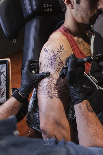 Master doing tattoo on forearm of male customer