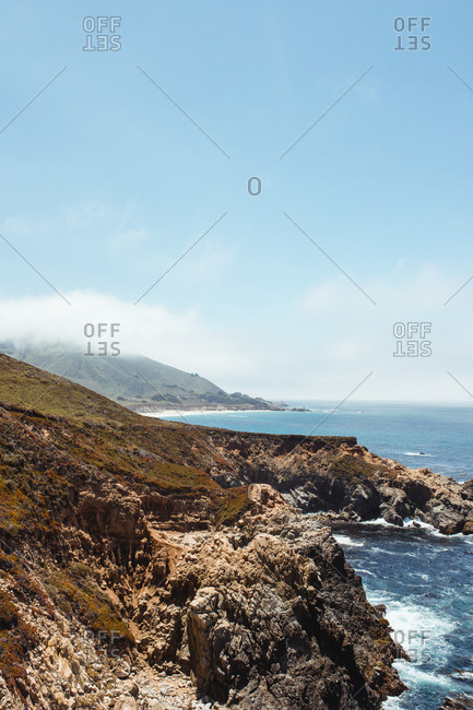 Empty stony rocky shore and clean blue water under light cloudy sky in Big Sur